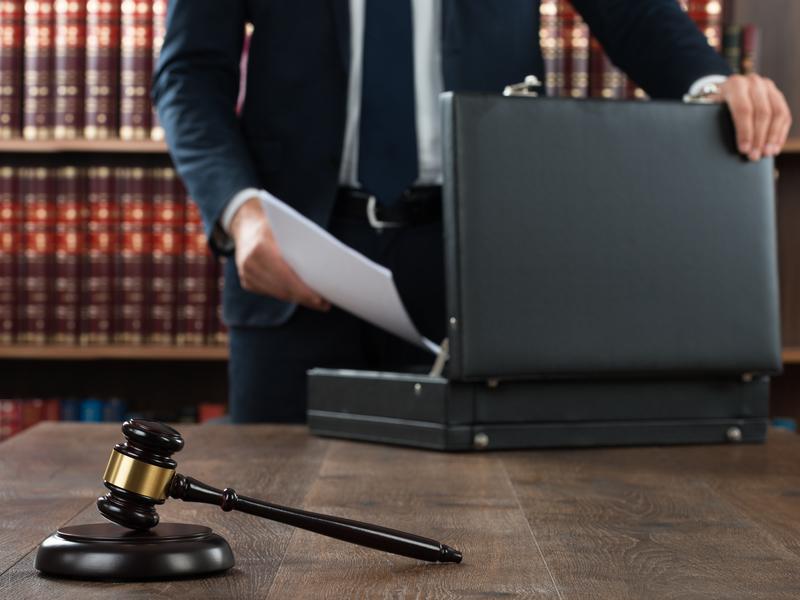 Un homme d'affaires rangeant des papiers dans une mallette posée sur une table sur laquelle se trouve également un marteau de justice.
