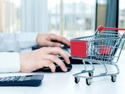 Un homme d'affaire devant son ordinateur, à côté on voit un chariot de magasin.