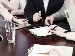 Plusieurs personnes assises autour d'une table regardant ensemble un document