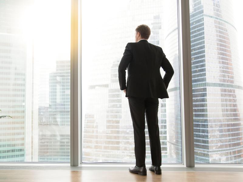 Un homme d'affaire devant une fenêtre.