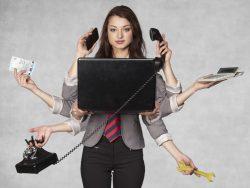 Une femme d'affaires devant un ordinateur. Elle a plusieurs mains, trois d'entre elles tiennent un téléphone, une autre une calculette, une un billet et la dernière une clé à molette.