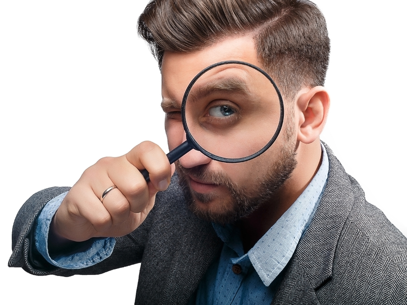 Un homme en costume avec une loupe posé contre l'oeil gauche.