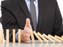 Un homme d'affaires arrêtant des dominos d'une main pour ne pas qu'ils fassent tomber les autres.