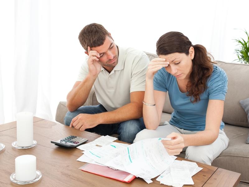 Un couple désespéré devant des feuilles de compte, une calculette est posée sur la petite table devant eux.
