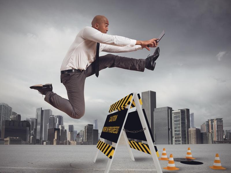 Un homme d'affaire faisant du saut à la haie par dessus un panneau attention et qui va tomber dans le vide.
