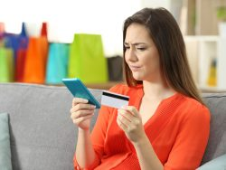 Une femme tenait une carte de crédit dans une main et son téléphone dans l'autre. Elle semble méfiante.