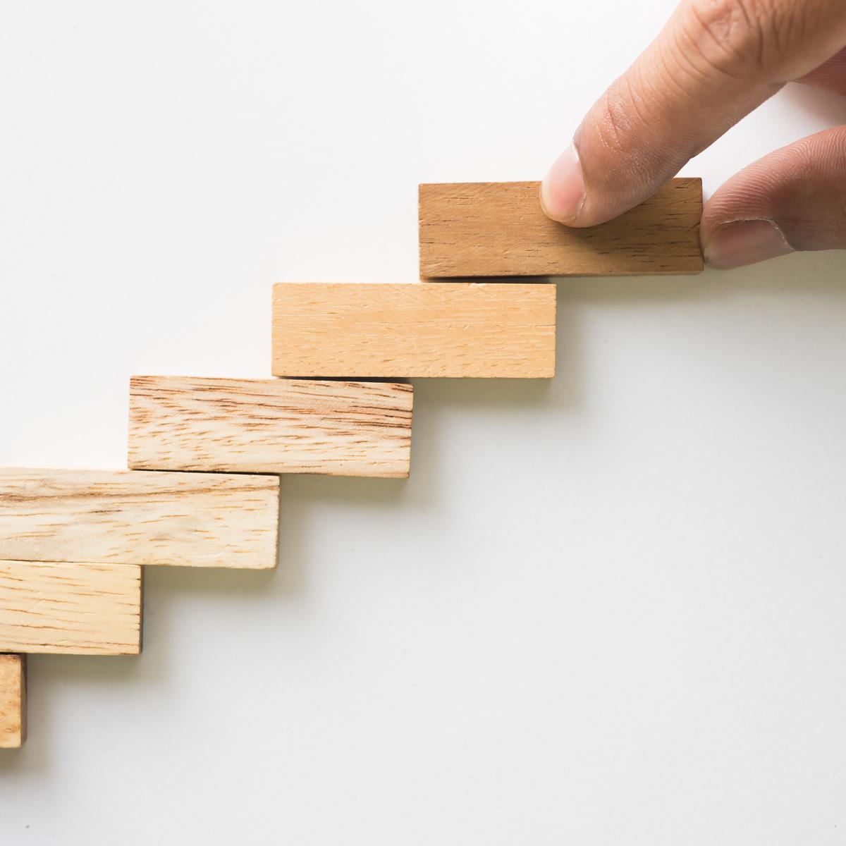 escalier fait en pièces de bois, une main ajoute une marche
