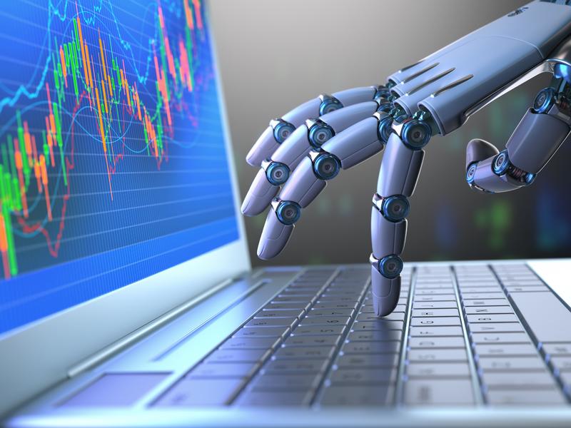 Une main de robot écrivant sur un clavier d'ordinateur.