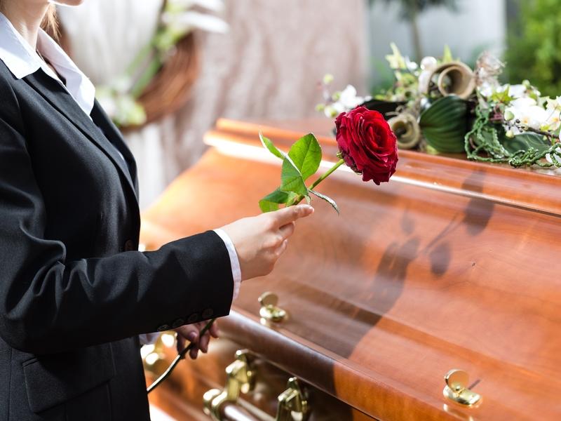 Une femme devant un cercueil avec une rose rouge.