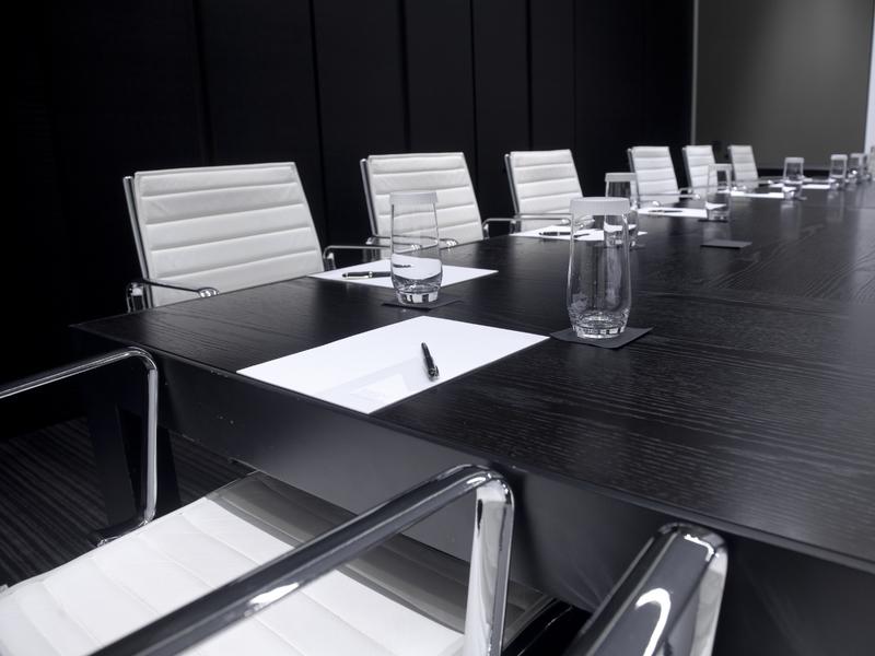Une salle avec une grande table et pleins de chaises autour.