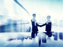 Deux hommes d'affaire se serrant la main en surimpression sur un paysage urbain
