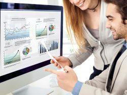 Un homme et une femme souriant regardant un rapport devant un ordinateur avec pleins de graphiques