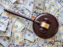 Un marteau de justice avec pleins de dollars en dessous.
