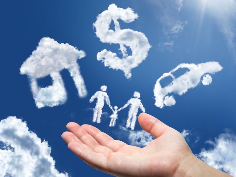 Une main dans le ciel avec des nuages en forme de dollar, de maison, de voiture et d'une famille