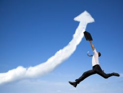Un homme d'affaire sautant en l'air dans un ciel bleu où des nuages dessinent la forme d'une flèche allant vers le haut.