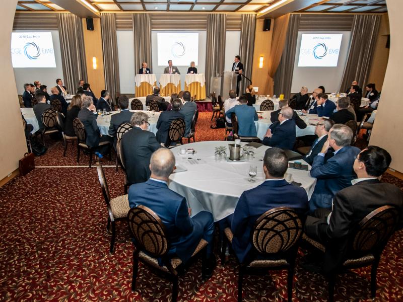 Une association de gestionnaires émergents assis à des tables et regardant vers la scène où se trouvent trois panellistes