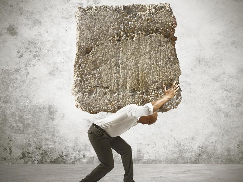 Homme d'affaire portant un très gros bloc de pierre