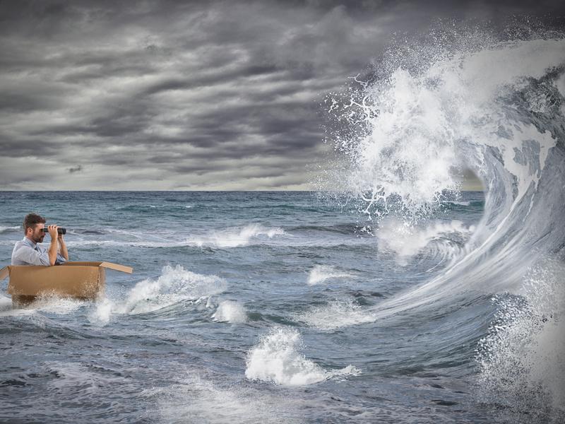 Homme d'affaire dans un carton sur la mer face à une vague
