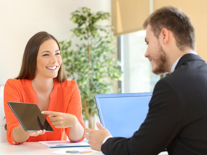 jeune femme souriante tenant une plquette dans sa main et la montrant à un homme d'affaire