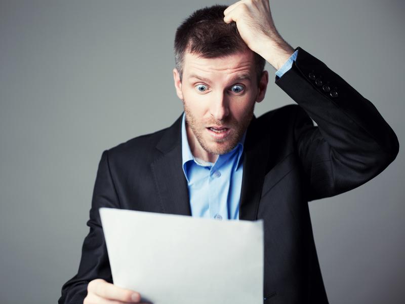 homme d'affaire apeuré lisant un document