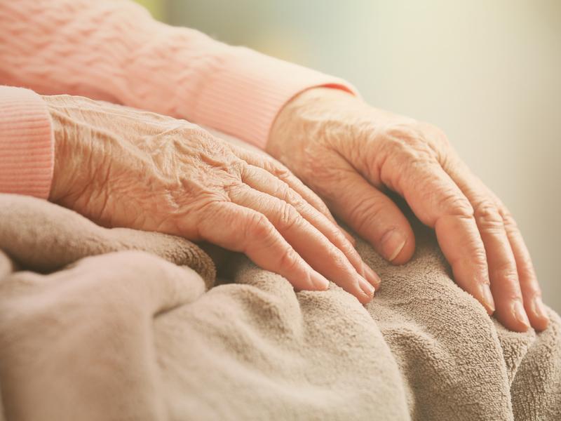 Une vieille femme, les mains posées sur les genoux