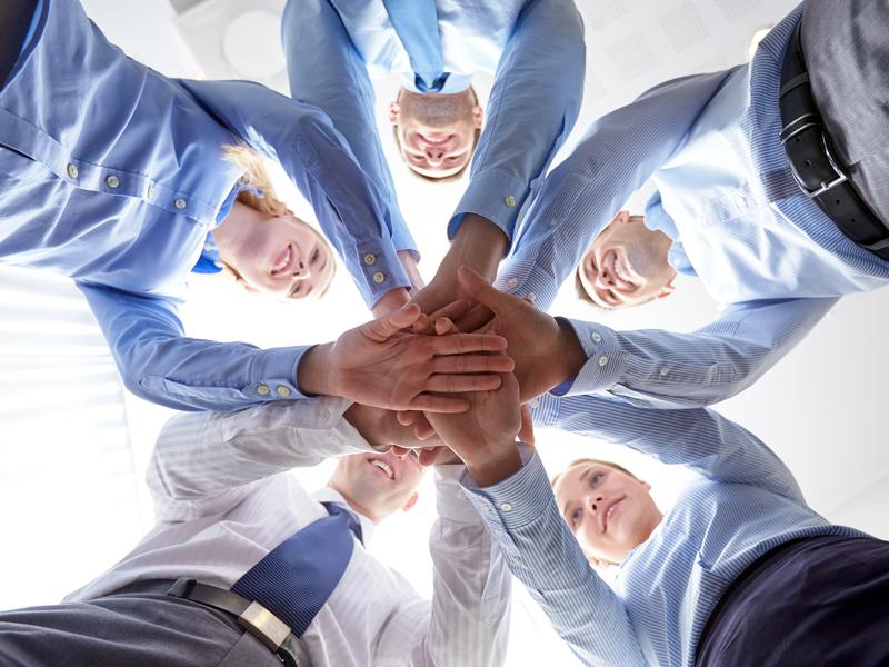 Un groupe d'hommes et de femmes d'affaire qui ont tous posé leurs mains les unes sur les autres