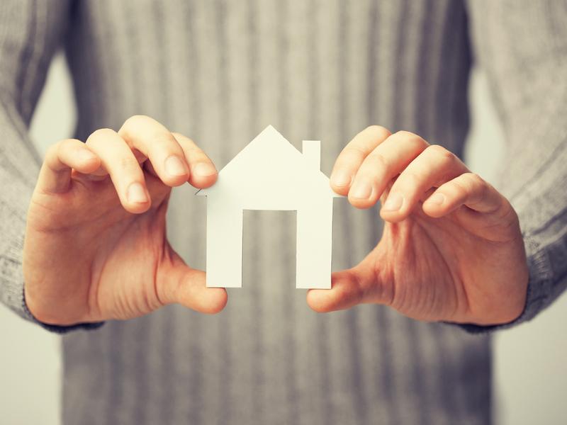 Une femme qui tient une petite maison en carton dans ses mains.