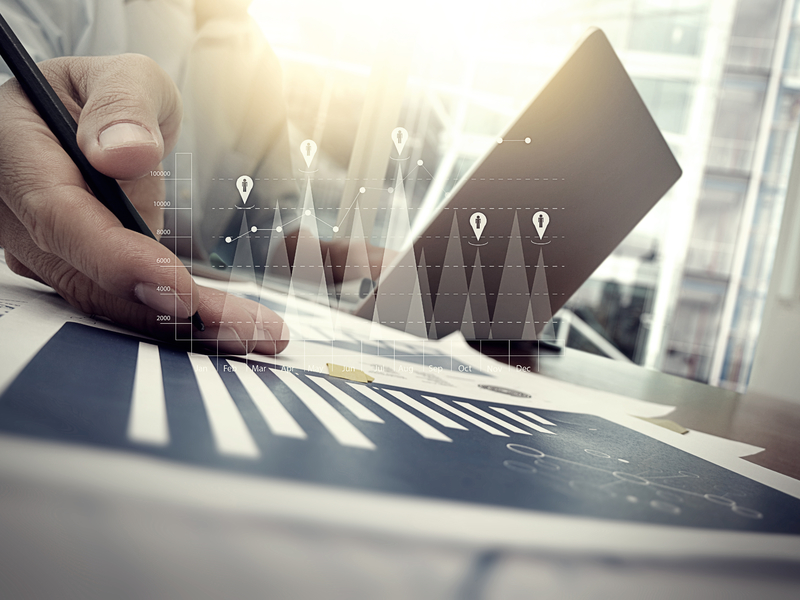 Un homme d'affaire devant un ordinateur montrant des graphiques financiers.