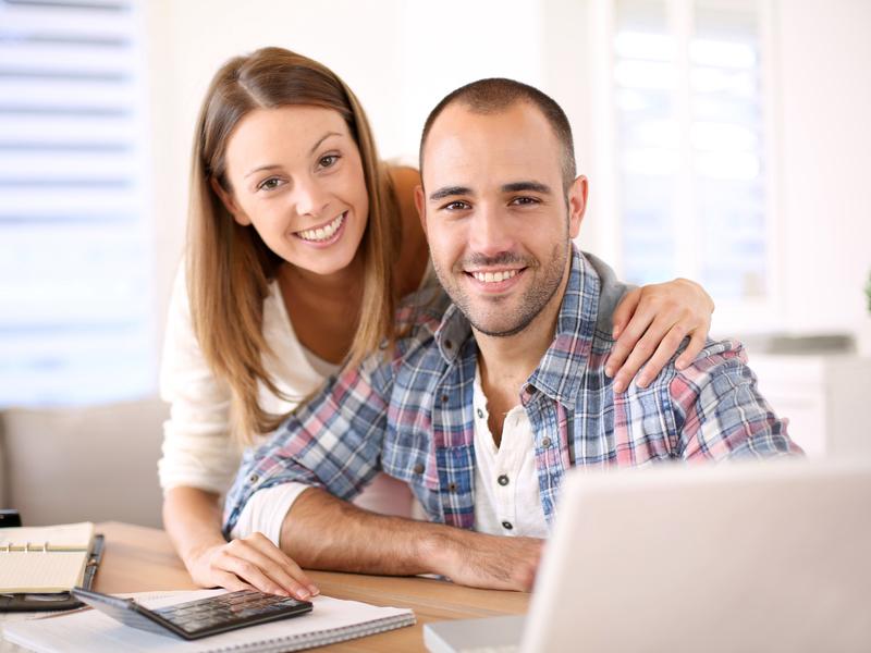 un couple souriant devant un ordinateur
