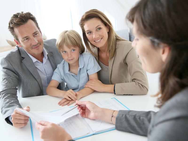 Une famille avec un père, une mère et un enfant qui regarde une conseillère qui leur explique des papiers.