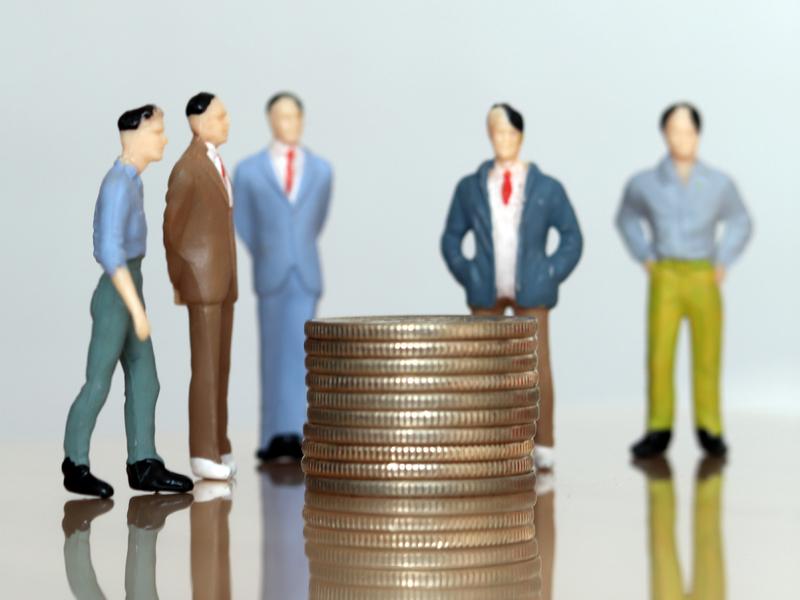 5 figurines représentant des hommes d'affaire debout devant un tas de pièces.