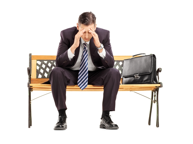 homme d'affaire assis sur un banc, se tenant la tête dans les mains.
