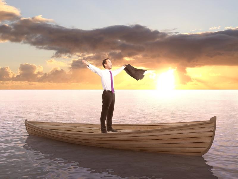 Homme d'affaire heureux, debout sur une barque au milieu de l'océan