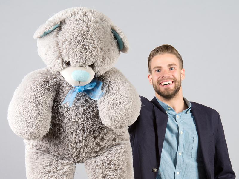 Homme souriant qui tend un gros ours en peluche.