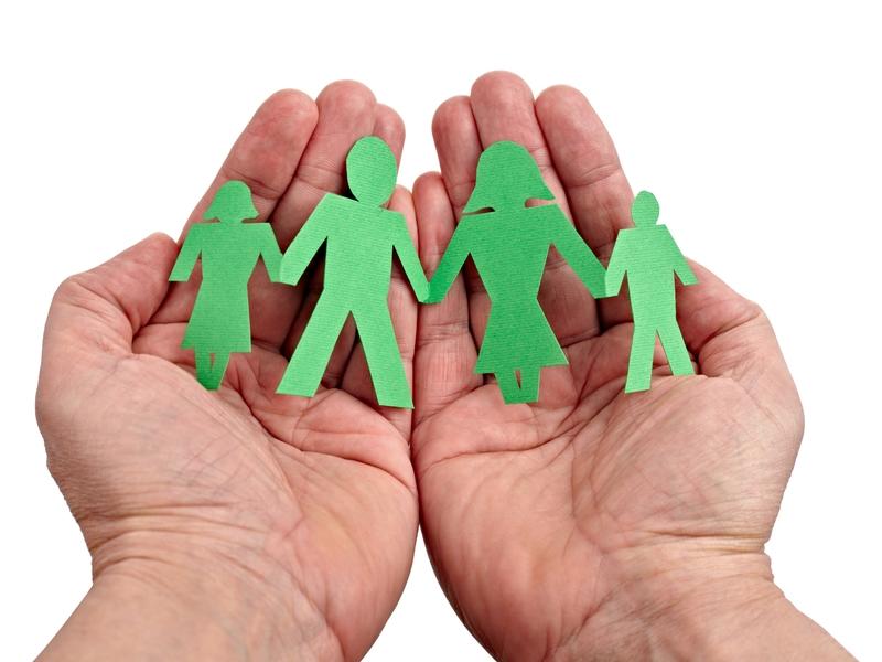 deux mains qui tiennent un découpage papier représentant une famille