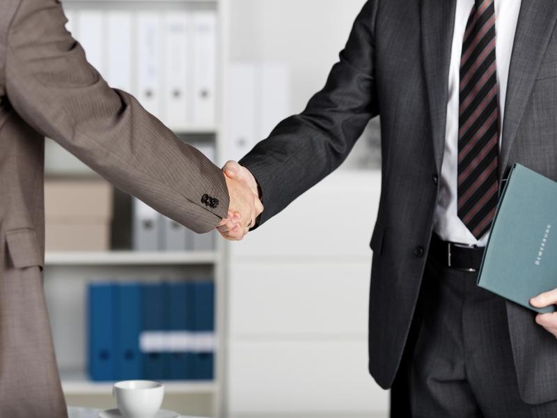Deux hommes en costume qui se serrent la main