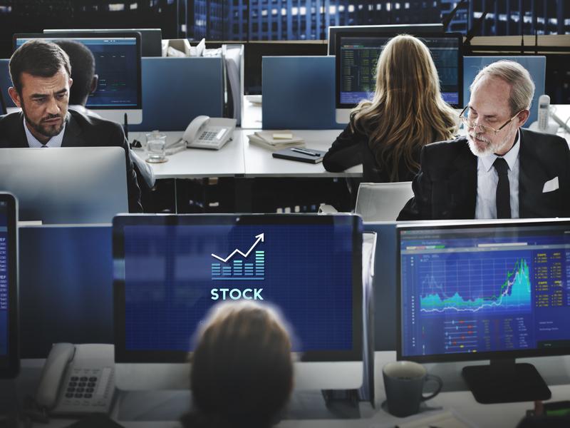 personnes assises devant des ordinateurs, dans une salle de la bourse