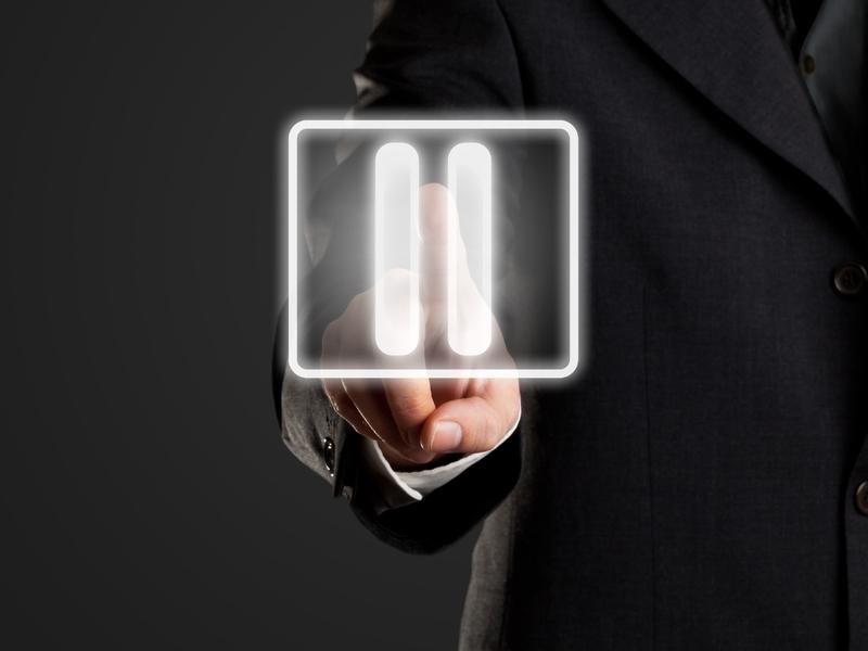 Un homme d'affaire posant un doigt sur le signe pause.