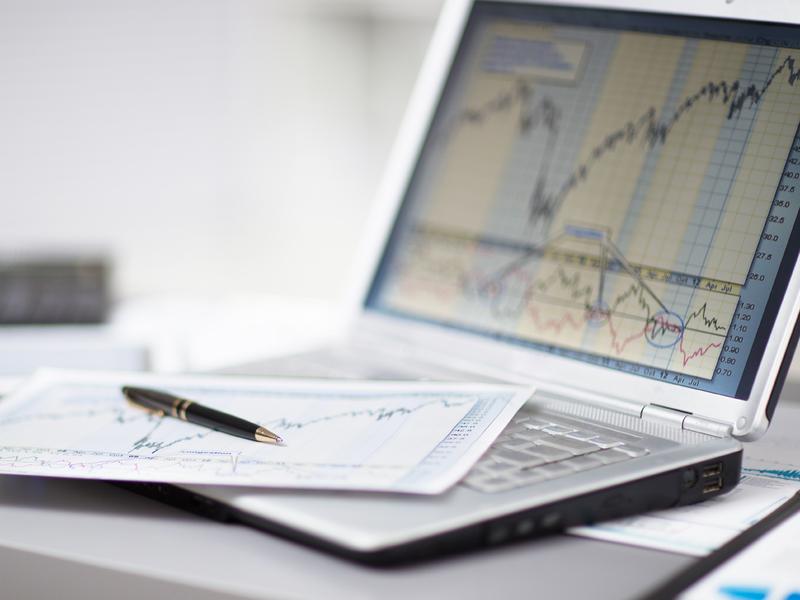 ordinateur avec des graphiques du marché dessus. Une feuille de papier et un stylo sont posés sur l'ordinateur.