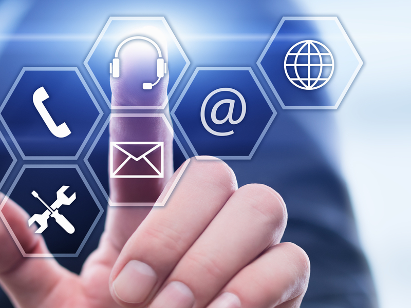 Homme d'affaire devant plusieurs logo représentant un téléphone, une enveloppe, internet qui appuie sur un logo de contact.