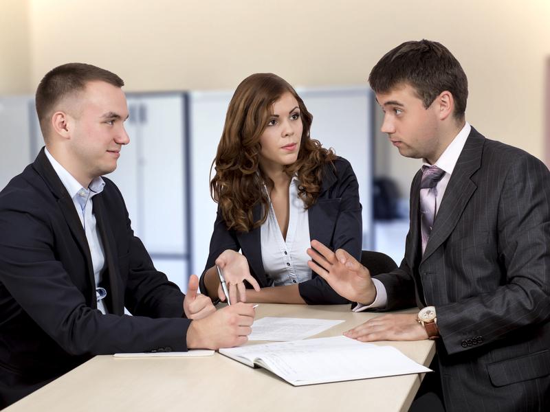 Réunion de trois hommes d'affaire, l'un d'eux semble émettre une objection.
