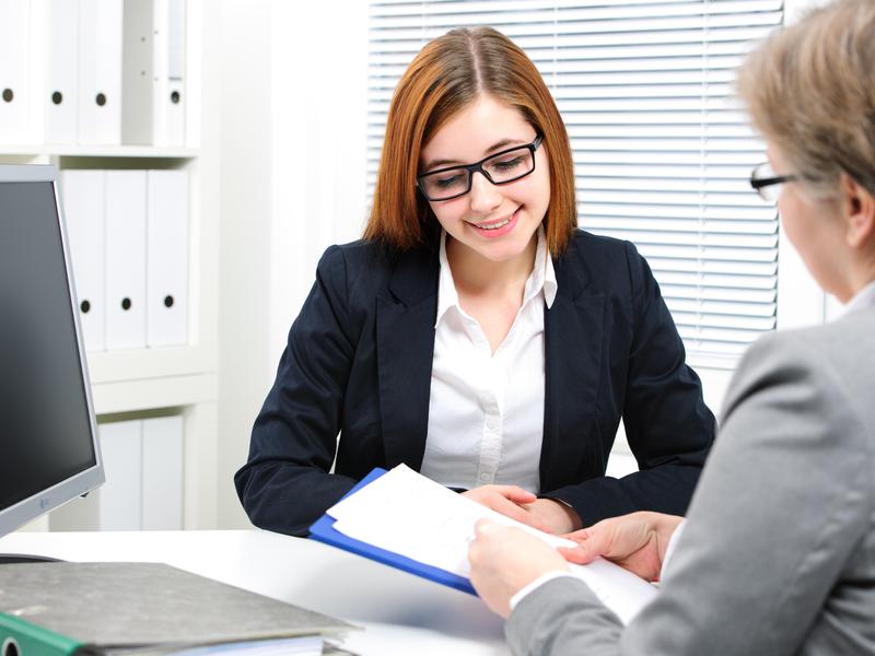 Une femme d'affaire souriante qui explique un document à une femme assise derrière son bureau.