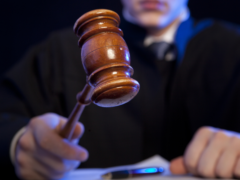 Un juge qui s'apprête à frapper son marteau.