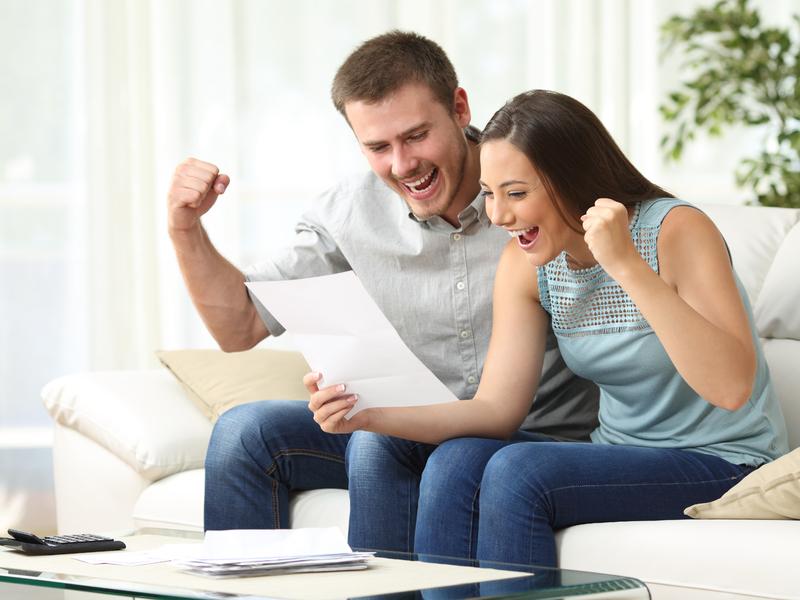 Un couple heureux qui regarde une feuille. Devant eux on voit une calculette