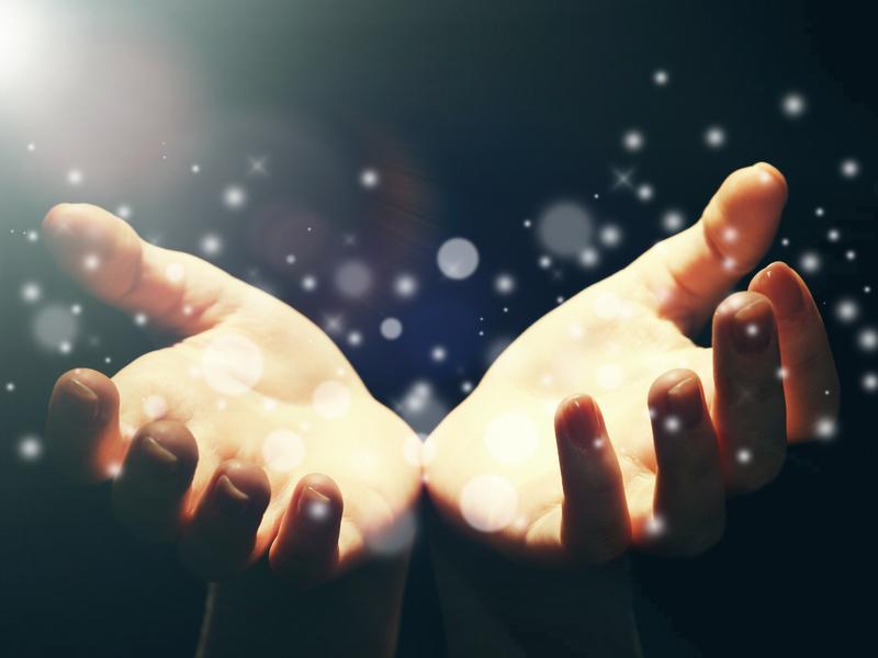 deux mains entourés de points lumineux avec une lumière miraculeuse qui les illumine.