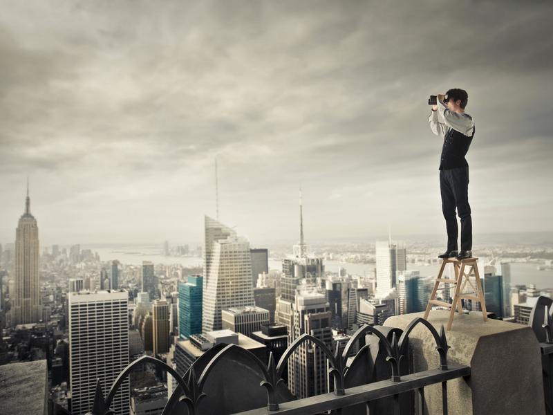 Un homme d'affaire sur un marche pied sur un toit qui regarde à l'horizon.
