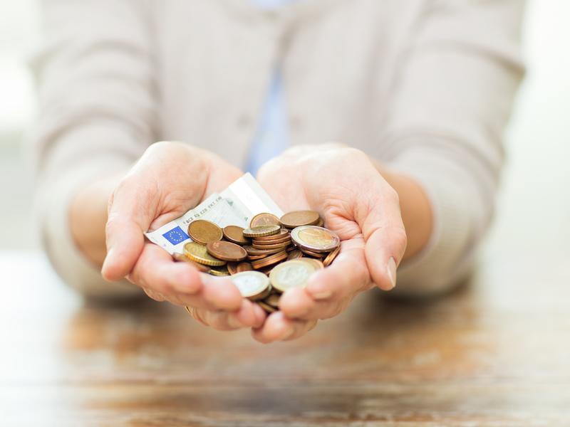 Une personne tendant les mains en coupe. Il y a plein d'argent dans ses mains.