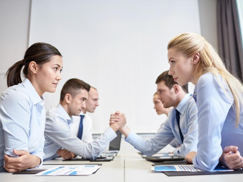 trois personnes d'un côté d'une table font face à trois autres. Ils semblent être en désaccord
