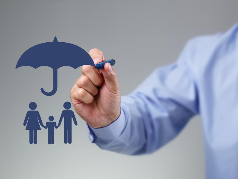 Un homme d'affaire avec un stylo qui retouche le dessin d'un parapluie protégeant une famille.