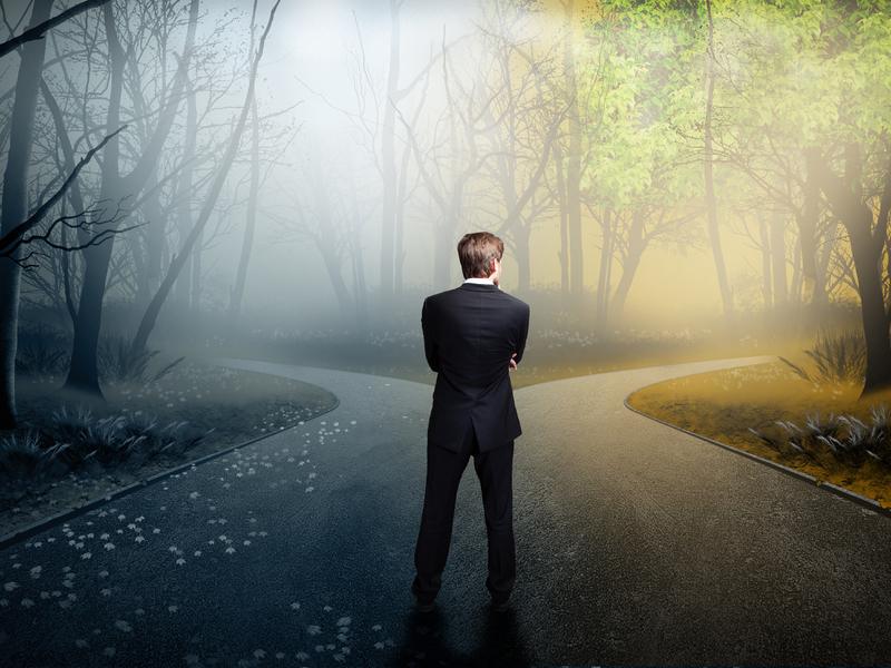 Un homme d'affaire qui hésite entre deux chemins dont un mène aux ténèbres et l'autre à la lumière